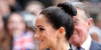 Meghan Markle cradles her baby bump during a visit to London City University Image GETTY