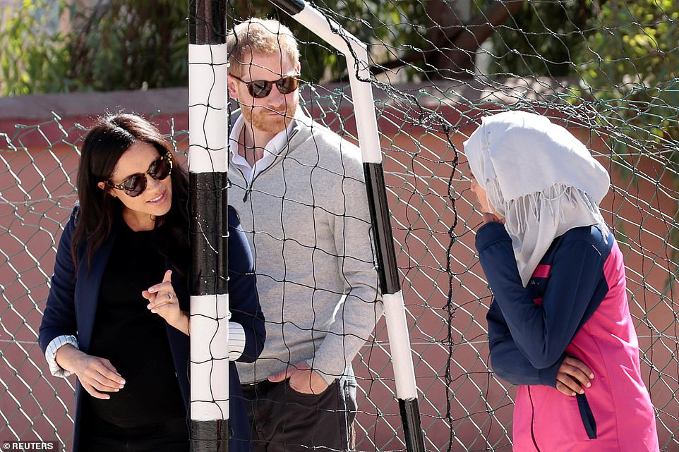 The couple watch a game of football as they visit a secondary school in Asni Morocco Meghan later changed into a smarter