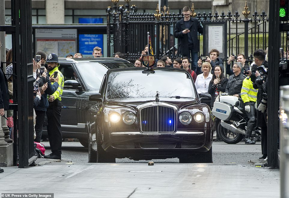 A crowd gathered to watch the royals drive through the gates into the campus of Bush House pictured