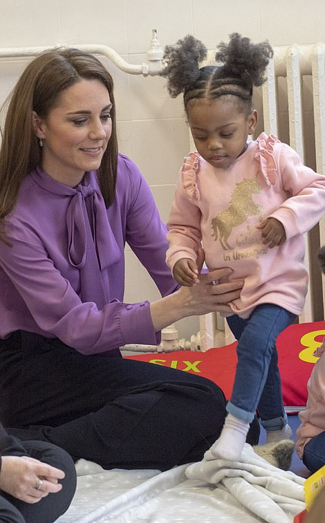 Adorable twins Kamina and Kashay left played happily around the Duchess Right Kate gives one of the girls a helping hand