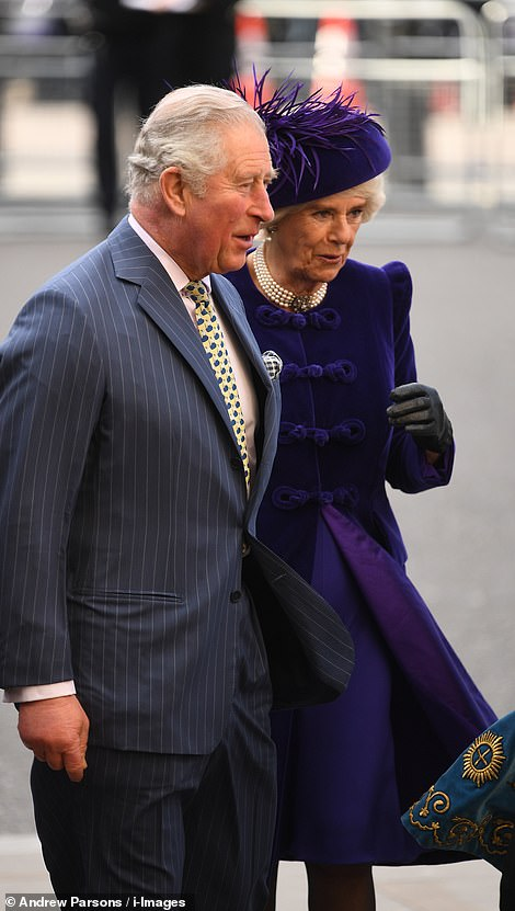 Camillas velvet knot tie coat blew open in the wind before she made her way inside with the Prince of Wales