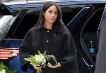 Meghan looked stunning in a black button down coat and heels Image Getty