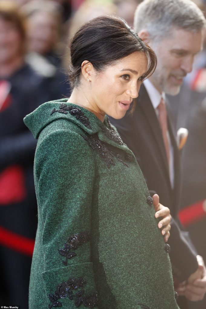 Meghan who is eight months pregnant wrapped up against the March chill with a bottle green wool dress featuring black beaded floral detail