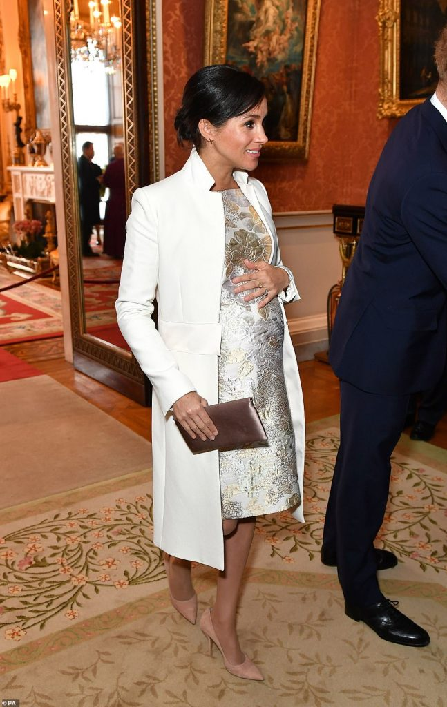 Meghan wore her hair in its signature relaxed bun coordinating her nude suede heels with a blush satin clutch bag as she arrived at the reception