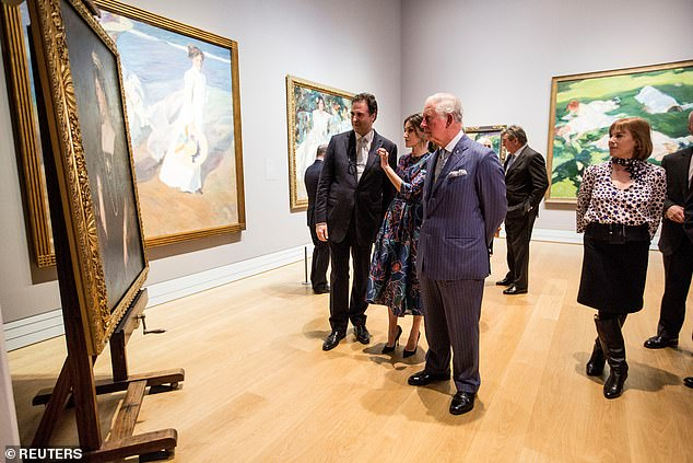 Queen Letizia admires one of the paintings while talking to Prince Charles and officials at the gallery