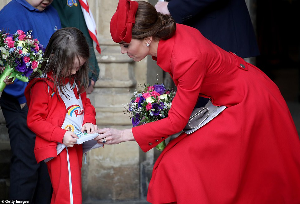 The Duchess of Cambridge clutched a colourful bouquet of flowers as she spoke to a young well wisher as she departed the Commonwealth Service