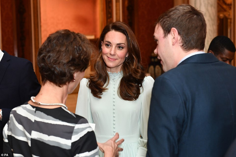 The Duchess of Cambridge speaks with guests at a reception at Buckingham Palace in London to mark the fiftieth anniversary of the investiture of the Prince of Wales