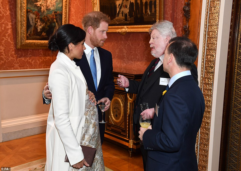 The Duchess of Sussex looked elegant as she joined Prince Harry chatting with Simon Weston and Alun Cairns and cradling her bump