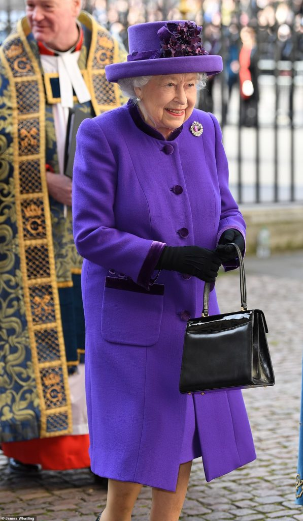 The Queen opted for a bold purple ensemble as she donned a matching hat and coat which she completed with a silver jewelled brooch and a patent black bag
