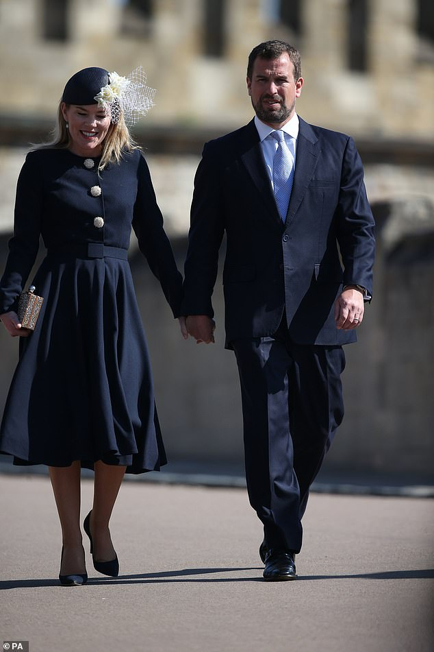 Autumn Phillips dressed in a chic navy belted coat dress Claire Mischevani and a navy and cream rose cocktail hat by milliner Julian Garner