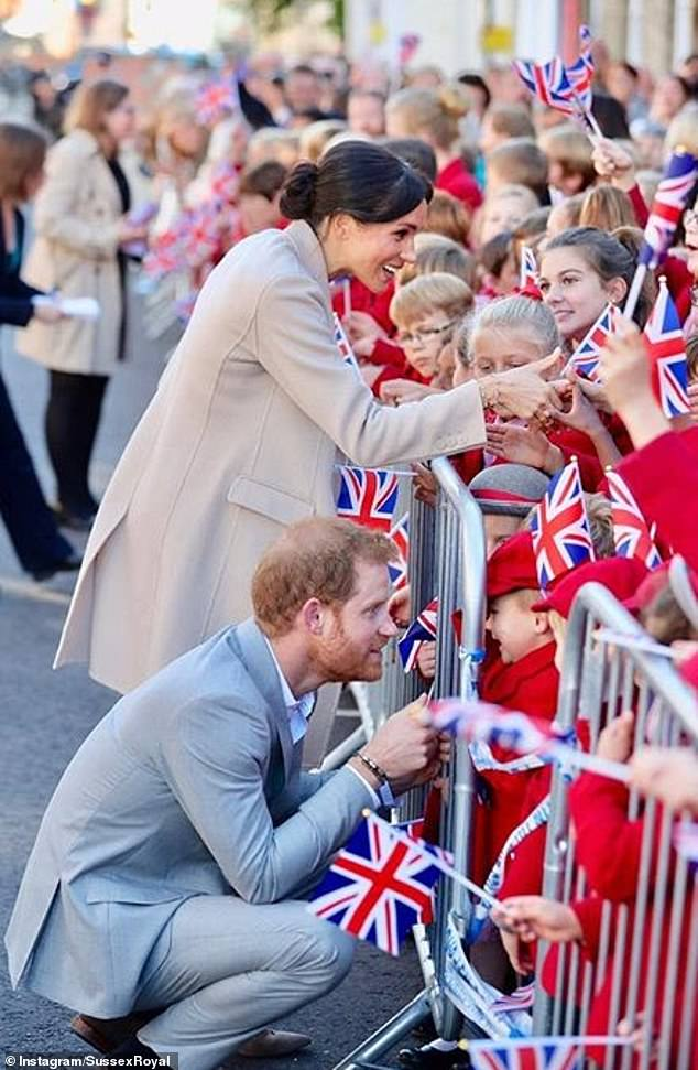 Harry and Meghan greeting schoolchildren during a visit to Sussex in October last year