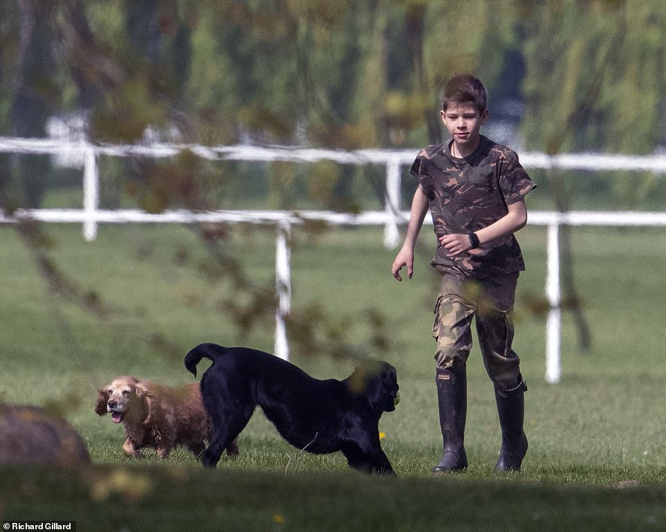 James who teamed his camo look with Hunter wellington boots followed in his mothers footsteps by throwing a tennis ball back and forth for the dogs