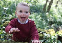 Little Louis pictured smiles broadly and cheekily reaches for the camera during the photoshoot at home with his mother Kate Middleton earlier this month
