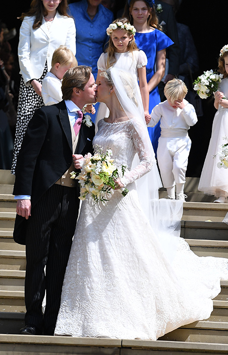 The happy couple kiss on the steps of the chapel after their private wedding ceremony Photo C iimage