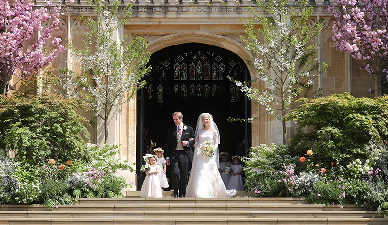The newlyweds smile as they exit the chapel with their young bridesmaids and pageboys Photo C iimage