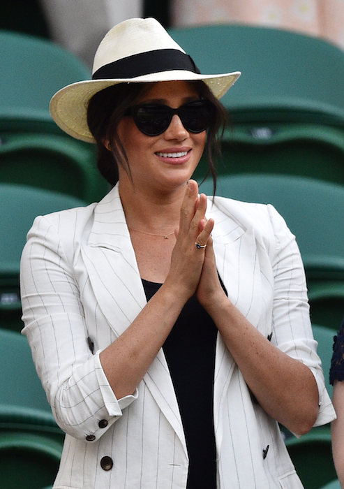 Meghan shaded from the sun in her Panama hat on Thursday Photo C Getty Images
