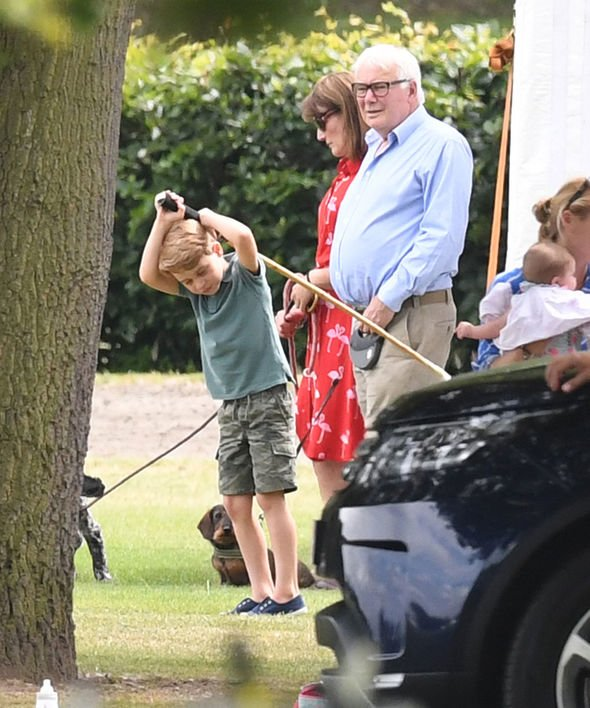 Prince George appeared to be having fun as he played with a polo mallet Image SPLASH