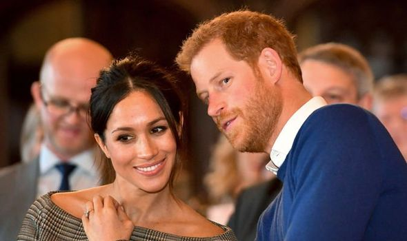 Prince Harry whispers to Meghan Markle as they watch a performance Image GETTY