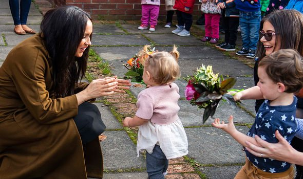 Meghan receiving flowers from a toddler