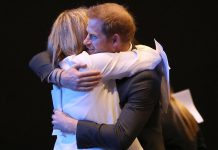 The Duke of Sussex is hugged during a sustainable tourism summit at the Edinburgh International Conference Centre today
