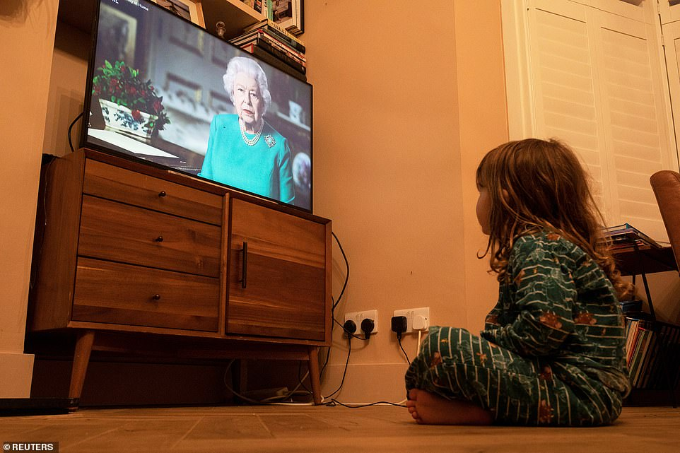 A girl in London watches Queen Elizabeth II during a televised address to the nation, as the spread of the coronavirus disease continues