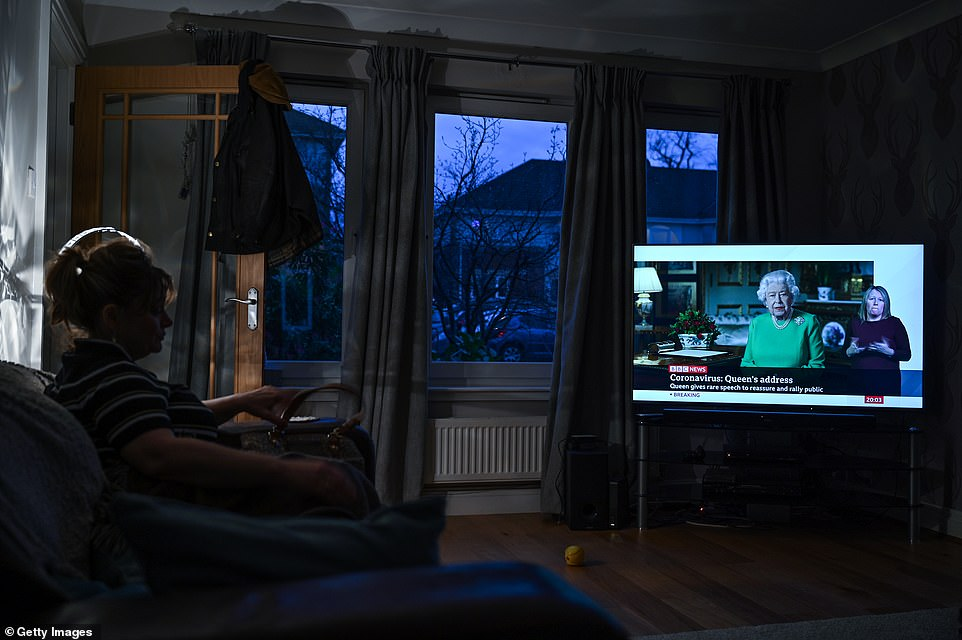 A woman in Glasgow watches Queen Elizabeth II speak in a rare televised address to the nation during the coronavirus crisis