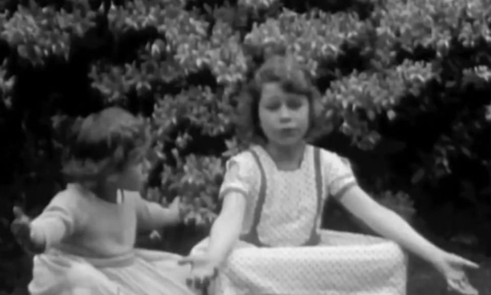 The Queen and Margaret are seen playing in a garden together in their younger years