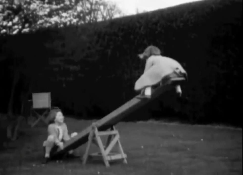Elizabeth and Margaret play on a seesaw in a garden when they were young children, in one of the clips released today