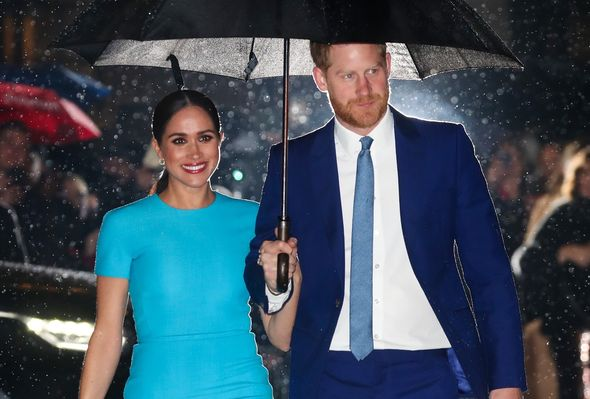 Prince Harry and Meghan Markle smile at cameras