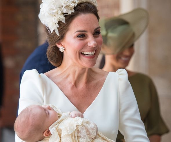 Catherine, Duchess of Cambridge carries Prince Louis as they arrive for his christening service