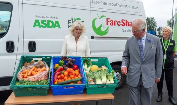 Prince Charles and the Duchess of Cornwall  stood with vegetables at event
