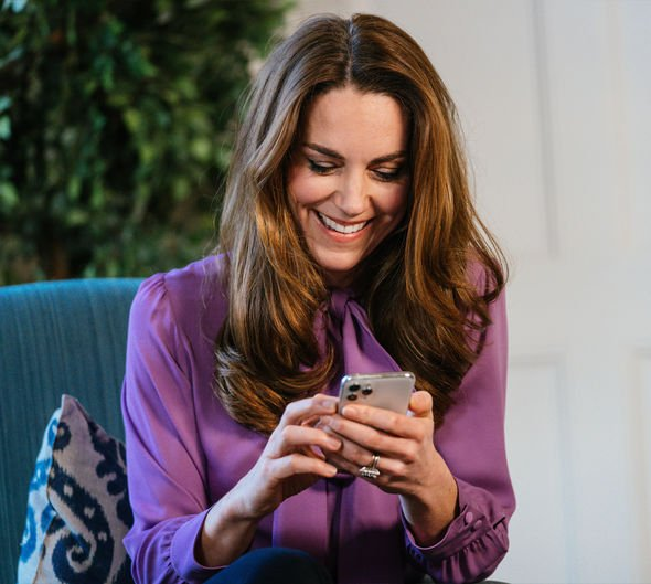 Kate smiling and looking at her phone