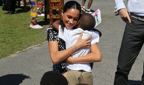 Meghan hugging a member of the public during a tour of southern Africa in 2019