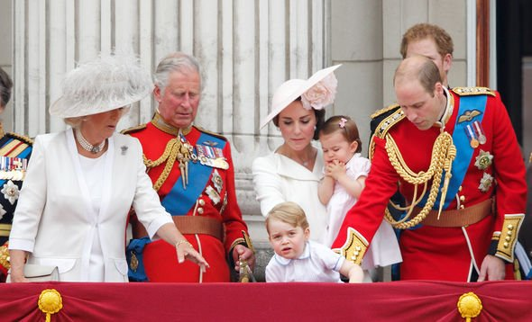 Prince George of Cambridge peers over the balcony of Buckingham Palace as Camilla, Duchess of Cornwall, Prince Charles, Prince of Wales, Catherine, Du