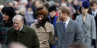 Prince Philip walks with Meghan Markle behind him