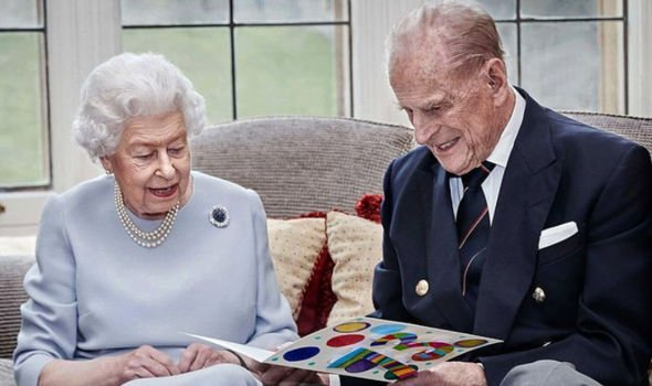 The Queen and Philip looking at a homemade card from the Cambridge children to honour their 73rd wedding anniversary