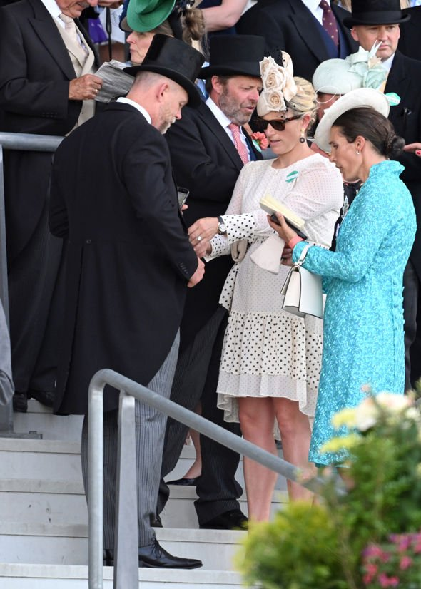 Zara Tindall and Mike: Zara appeared to help Mike with a wardrobe malfunction as they stood in the stands(Image: GETTY)